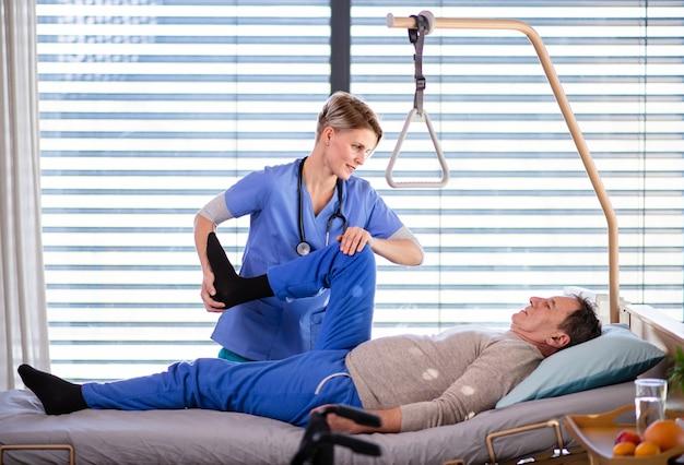 Un travailleur de la santé et un patient âgé à l'hôpital, concept de physiothérapie.