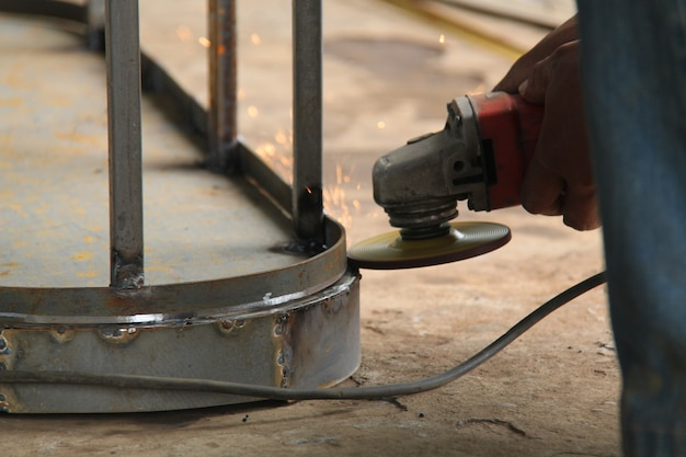 Travailleur sciant le métal avec un broyeur, des étincelles volent