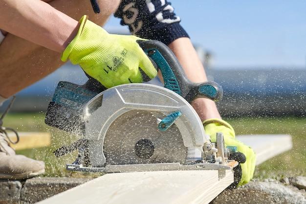 Travailleur sciant une planche de bois avec une scie circulaire électrique charpentier travaillant avec une scie circulaire à l'extérieur en journée ensoleillée en gros plan