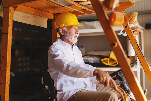 Travailleur senior barbu en uniforme et avec un casque de protection sur la tête d'un chariot élévateur en entreposage.