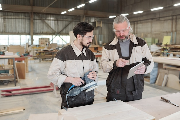 Travailleur senior de l'usine moderne à l'aide du pavé tactile tout en expliquant à son jeune collègue comment traiter la pièce en bois avec broyeur