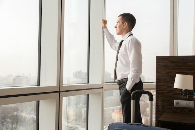 Travailleur sérieux regardant la ville à travers la fenêtre