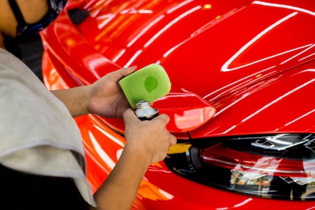 Travailleur de service automobile appliquant un revêtement nano sur un détail de voiture