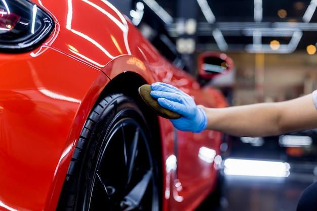 Travailleur de service automobile polissage des roues de voiture avec un chiffon en microfibre.