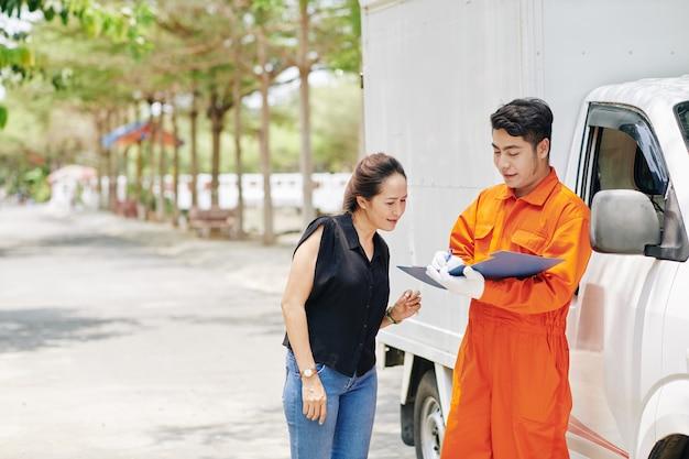 Travailleur de service de déménagement prenant des notes