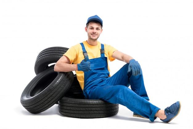 Travailleur de service en uniforme bleu assis sur des pneus de voiture, fond blanc, réparateur de pneus, montage de roue