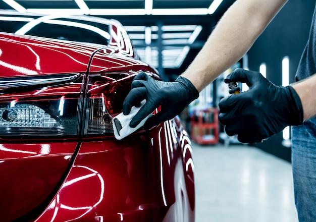 Travailleur de service de voiture appliquant un revêtement nano sur un détail de voiture.