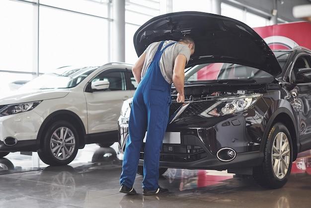 Travailleur de service de voiture musculaire réparant le véhicule.