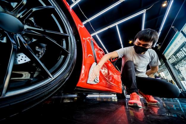 Travailleur de service de voiture polissant la voiture avec un chiffon en microfibre.