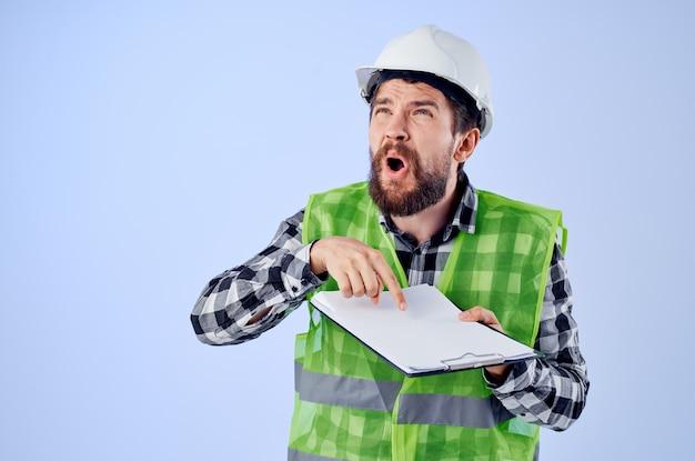 Travailleur de sexe masculin dans un casque blanc blueprints fond bleu professionnel