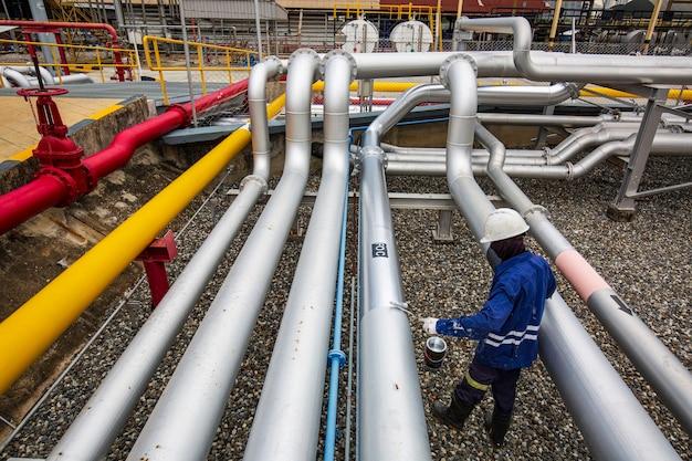 Travailleur de sexe masculin peint en gris à la vanne d'écoulement d'huile de pipeline