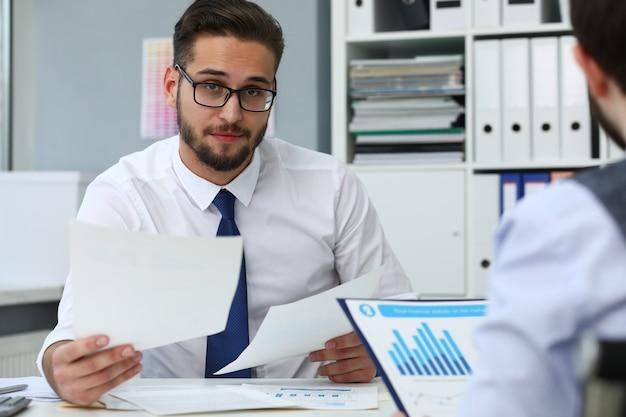 Travailleur de sexe masculin tenant des documents dans les mains au bureau