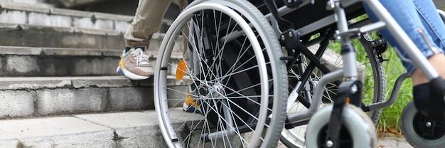 Un travailleur social aide une personne handicapée en fauteuil roulant à monter les escaliers concept