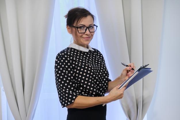 Travailleur social femme mature, psychologue près de la fenêtre avec presse-papiers