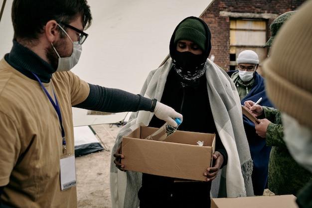 Travailleur social en masque et lunettes mettant une bouteille d'eau dans une boîte tenue par un réfugié du moyen-orient avec un plaid sur les épaules
