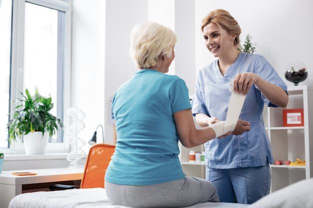 Travailleur de soins médicaux. belle infirmière sympathique souriant à son patient tout en faisant son travail à l'hôpital