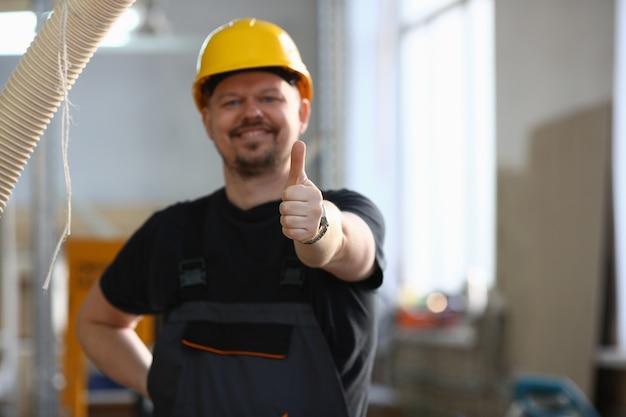 Travailleur souriant en casque jaune montrer confirmer signe