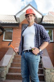 Travailleur souriant posant devant la maison avec escalier en pierre