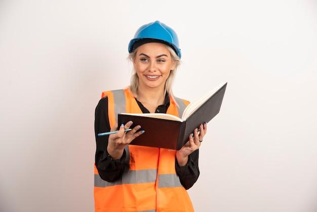 Travailleur souriant tenant un cahier sur fond blanc. photo de haute qualité