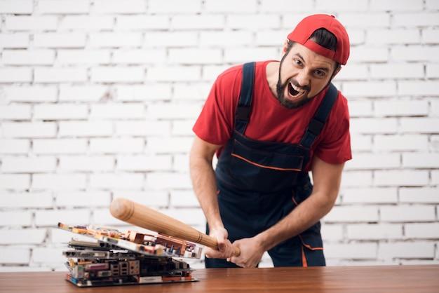 Un travailleur stressé ruine des tableaux de pc avec une batte de baseball.