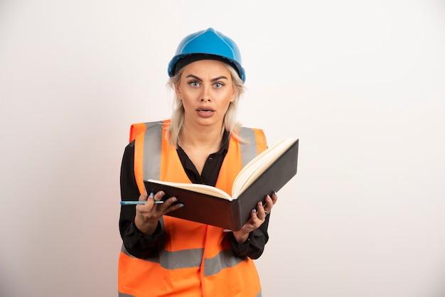 Travailleur surpris tenant un cahier sur fond blanc. photo de haute qualité