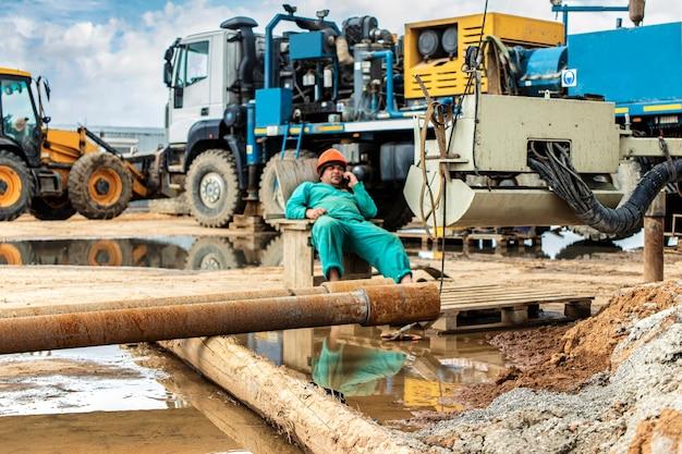 Un travailleur surveille le processus de forage d'un puits sur un chantier de construction. forage profond. exploration de minéraux utiles. industrie et bâtiment.