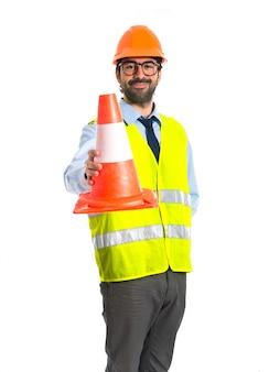 Travailleur tenant un cône de trafic
