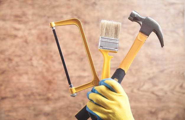 Travailleur tenant un marteau, une scie, une brosse.
