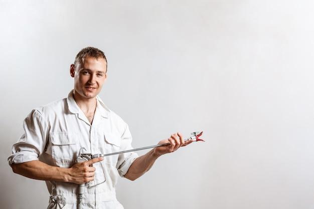 Travailleur tenant le pistolet pulvérisateur sur mur blanc.