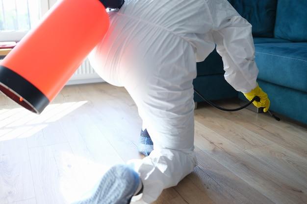 Travailleur en tenue de protection traitant avec une solution désinfectante sur le sol sous un canapé dans un appartement