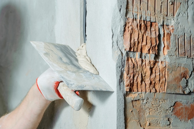 Un travailleur tient des truelles avec du gypse. il recouvre les tubes ondulés électriques dans le mur.