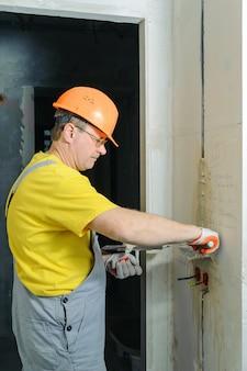 Le travailleur tient des truelles avec du gypse. il recouvre les tubes ondulés électriques dans le mur.