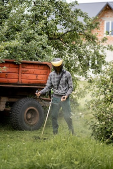 Travailleur avec une tondeuse à essence dans ses mains, tondre l'herbe devant la maison. tondeuse entre les mains d'un homme.