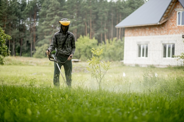 Travailleur une tondeuse à essence dans ses mains, tondre l'herbe devant la maison.