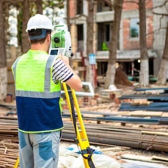 Travailleur de la topographie de la construction sur le chantier