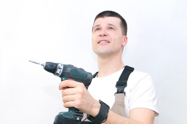 Le travailleur a un tournevis dans ses mains. technicien en salopette spécialisée