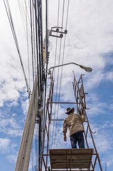 Travailleur travaillant pour installer une ligne électrique
