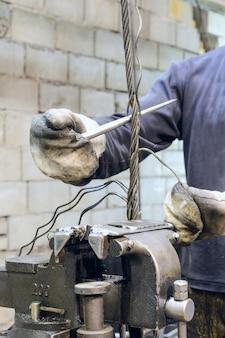 Le travailleur tresse l'extrémité des élingues en câble d'acier. fabrication d'élingues en câble métallique.