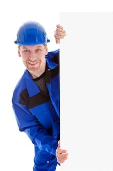 Le travailleur en uniforme bleu tenant le panneau d'affichage vierge