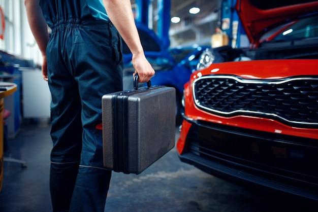 Travailleur en uniforme est titulaire d'une boîte à outils, station-service de voiture. contrôle et inspection automobile, diagnostic et réparation professionnels