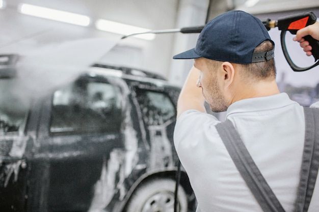 Travailleur en uniforme gris sur une voiture noire recouverte de mousse. il tient un tuyau flexible avec un pistolet dessus et lave une automobile. l'homme est sérieux et concentré. il est dans le garage.
