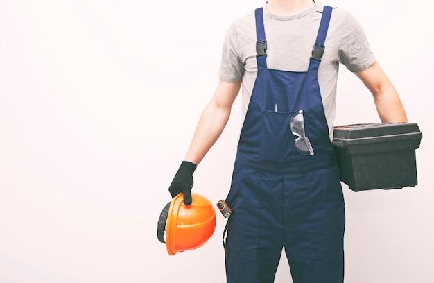 Travailleur en uniforme professionnel avec boîte à outils à la main sur fond gris