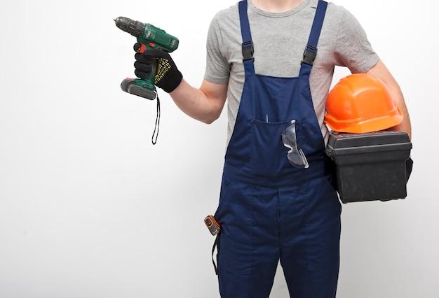 Travailleur en uniforme professionnel avec boîte à outils à la main sur gris
