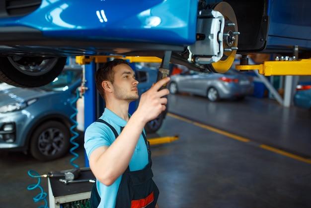 Travailleur en uniforme vérifie la suspension du véhicule sur l'ascenseur, la station-service de voiture. contrôle et inspection automobile, diagnostic et réparation professionnels