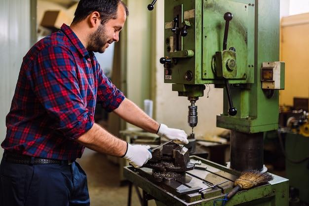 Travailleur utilisant une lime métallique dans une usine