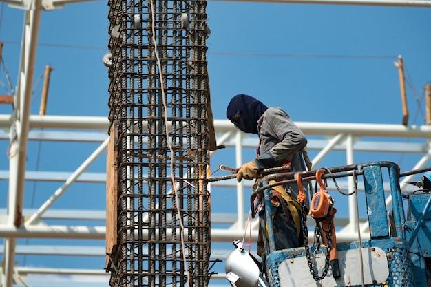 Travailleur utilisant la meule électrique sur la structure en acier en usine. travailler en haut