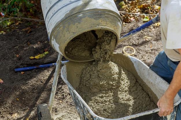 Travailleur utilise un béton fait dans la bétonnière lors de travaux de construction