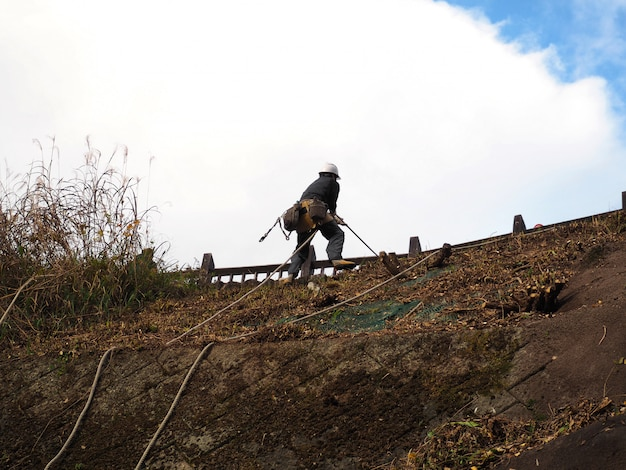 Travailleur utilise des équipements grimpant à la montagne.