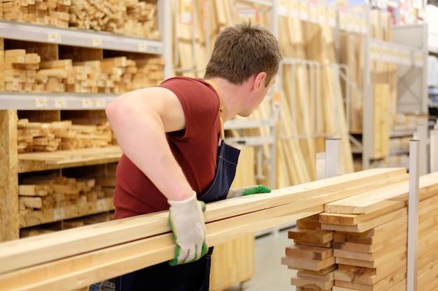 Travailleur ou vendeur dans le magasin de construction ou le département du bois de l'entrepôt au travail