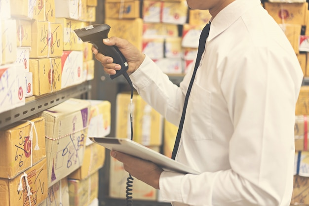 Travailleur vérifiant et numérisant le paquet dans l'entrepôt.